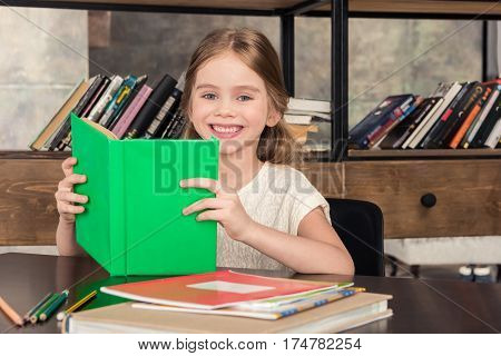 Cute little schoolgirl holding book and smiling at camera