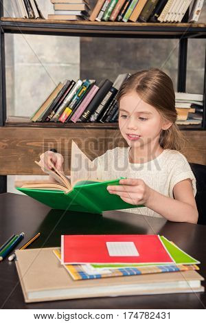 Cute smiling schoolgirl sitting at table and reading book in library
