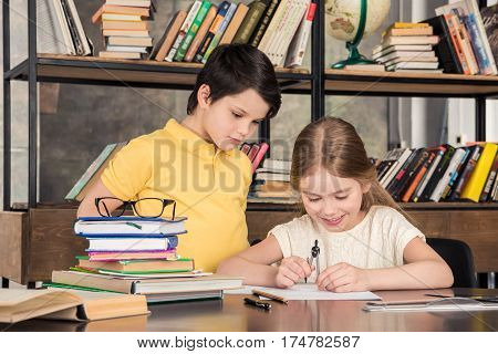 Cute little schoolchildren studying in library together