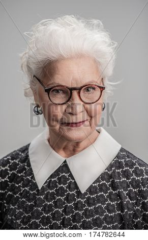 Imagination has no age. Portrait of beautiful senior woman with white hair wearing eyeglasses isolated on gray background