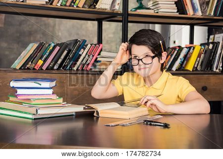 Schoolboy in eyeglasses sitting at table with books and studying in library
