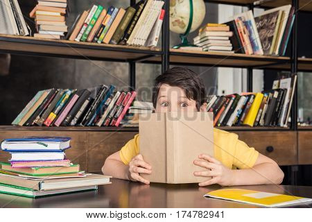 Shocked schoolboy peering over book in library