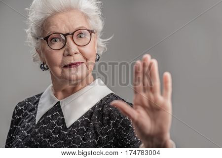 Best is yet to come. Portrait of senior woman holding out palm of hand. Isolated
