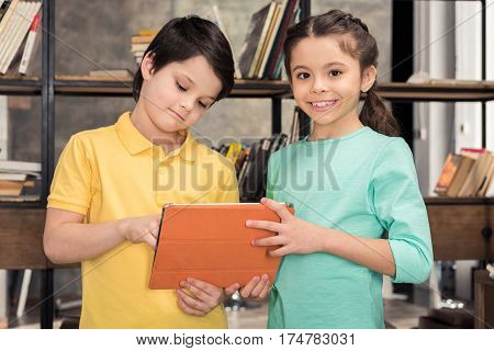 Cute smiling schoolchildren using digital tablet together