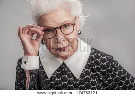 Say it again. Portrait of Serious elderly woman posing at camera while holding glasses by her hand. isolated on gray background
