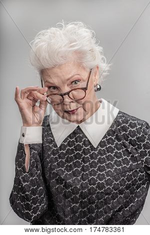 Sometimes arguments are necessary. Waist up portrait of Mature white haired woman looking over rim of glasses while standing. isolated on gray background