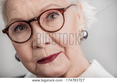 Lost in thought. Close up portrait of beautiful senior woman daydreaming while staring upwards with gentle smile. isolated on gray background