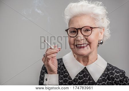 This is my life. Waist up portrait of Happy elderly woman in trendy glasses holding cigarette and smiling at camera. isolated on gray background. Copy space in left side