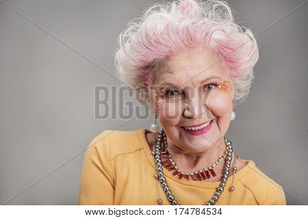 Always happy. Portrait of Joyful attractive elderly woman smiling with bright makeup and jewelry. isolated on gray background. Copy space