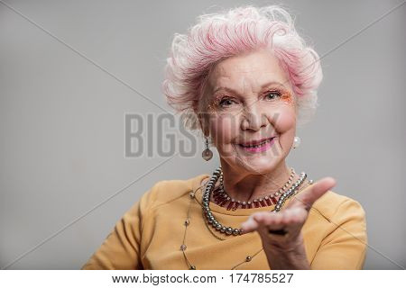 Feeling loved. Waist up portrait of Smiling senior female showing air kiss while posing. isolated on gray background