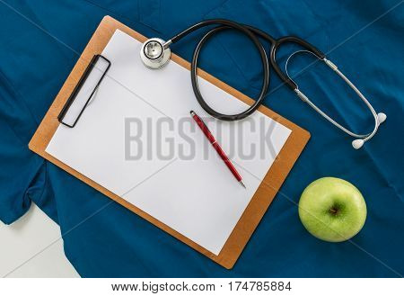 Clipboard with stethoscope on doctor's shirt background