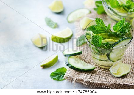Healthcare, fitness, healthy nutrition concept. Fresh cool cucumber lime mint infused water, cocktail, detox drink, lemonade for spring summer days. Copy space background
