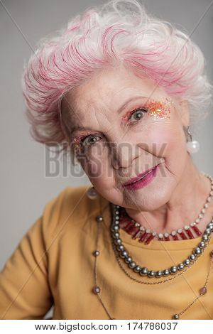 Look good and feel good. Close up portrait of graciously senior woman with white hair and yellow dress. isolated on gray background