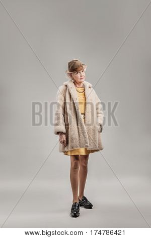 Live your life. Full length portrait of Senior woman in expensive fur coat posing. isolated on gray background
