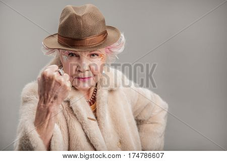 Just wait till I get you. Portrait of angry elderly female wearing fur coat and showing fist up with negative facial expression. isolated on gray background