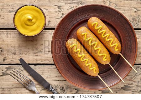 Corn dog traditional American fast food fried sausages in cornmeal batter on stick with mustard snack treat on rustic wooden table