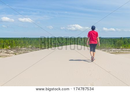 Girl walking over dune with Forest of Pinus Elliottii in background at Lagoa dos Patos lake coast
