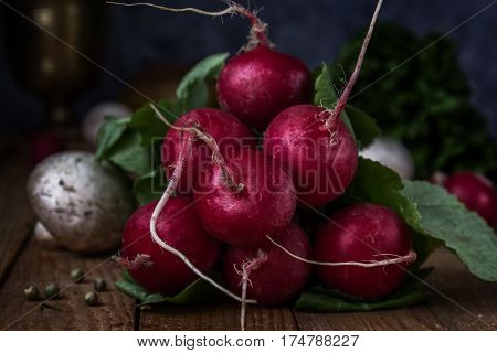 Radishes on wooden boards. Still life. Rustic, moonlight, magical light, low key