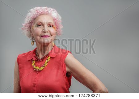 Ageing with confidence. Waist up portrait of Happy stylish elderly female in red dress and jewelry standing. isolated on gray background. Copy space