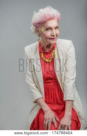Enjoying her golden years. Portrait of Smiling positive senior woman wearing red dress and white jacket looking at camera while sitting. isolated on gray background