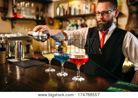 Barman making alcohol cocktails in nightclub