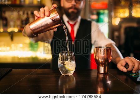 Bartender is making alcohol cocktail at counter