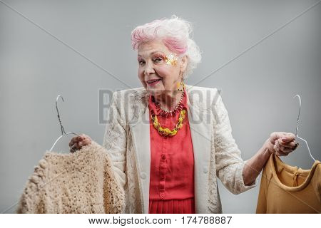 I do not know what to choose. Senior happy elegant woman choosing dress while standing. isolated on gray background