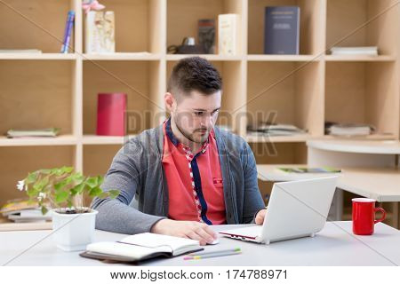 Man in casual grey Jacket and red Shirt working on white portable Computer sitting at grey Table with Flower and Business and Lifestyle Items on wood Wall background.