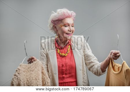 Thinking back on the good old days. Portrait of Happy beautiful elderly lady in red dress and jewelry holding and choosing dress while posing. isolated on gray background