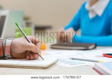 Simple Business Composition with Papers Charts and Hand of Man making Notes in Notepad with color Pencil