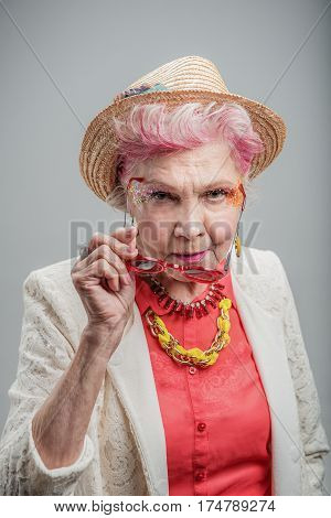 My style today. Portrait of Trendy attractive elderly lady holding sunglasses in front of her. isolated on gray background