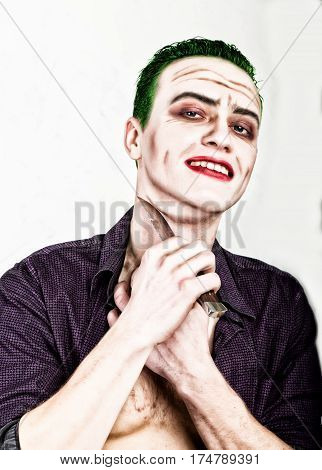 guy with crazy joker face holding knife, green hair and idiotic smike. carnaval costume.