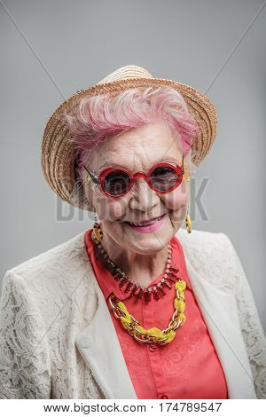 Senior but still smiling. Portrait of Beautiful senior woman wearing sunglasses and hat while standing against gray background