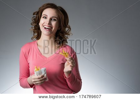 young beautiful girl with a French fries from a fast food smiling on a gray background