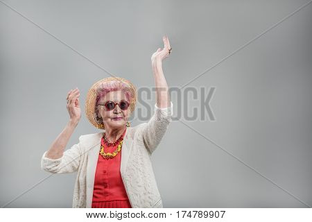 I want to move. Happy stylish senior lady in hat dancing with hands raised and smiling isolated on gray background