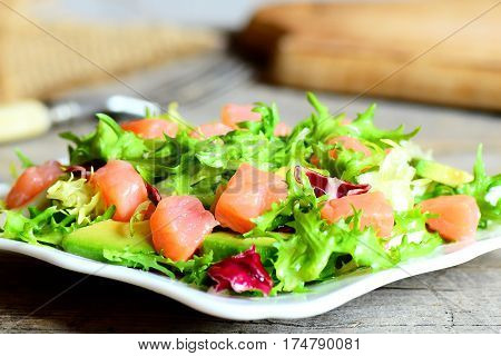 Delicious and simple salmon salad on a plate. Salad prepared with smoked salmon, salad mix and fresh avocado and dressing with olive oil and lemon juice. Vintage style. Closeup