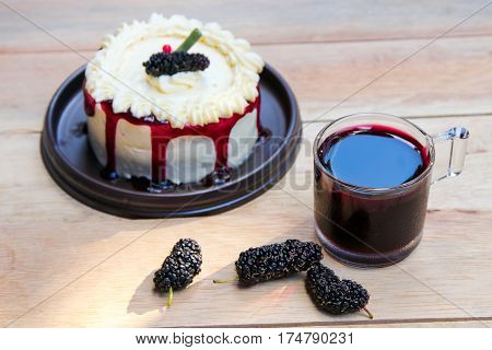 vanilla cake with mulberry and mulberry juice on wood background.