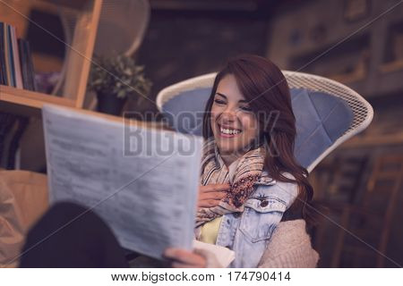 Young woman sitting in a cafe surprised and happy while reading a newspapers