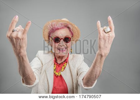 It take long time to get this cool. Happy smiling elderly female showing rock-and-roll sign. She wearing sunglasses and doing funky action isolated on gray background