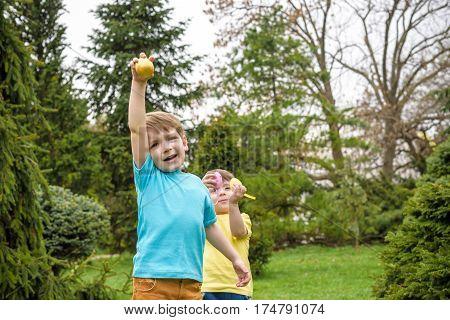 Kids On Easter Egg Hunt In Blooming Spring Garden. Children Searching For Colorful Eggs In Flower Me