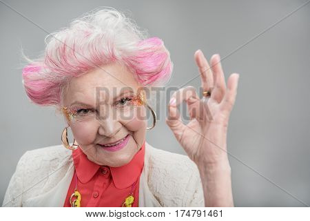 Everything is fine. Smiling attractive elderly woman with pink hair showing okay while standing in studio isolated on gray background