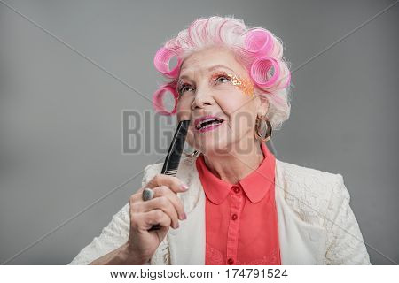 My favorite song. Cheerful attractive senior woman singing while holding comb like microphone in studio over gray background