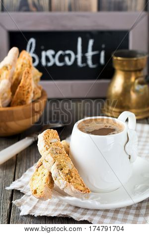 Homemade biscotti with nuts and a cup of coffee on the old wooden table background. Selective focus.
