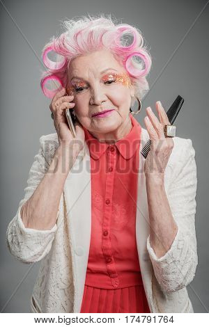Always connected. Attractive blond middle age woman talking by smartphone attentively while holding comb in her hand. isolated on gray background