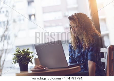 Young woman sitting in a cafe having a cup of coffee and working on a laptop computer