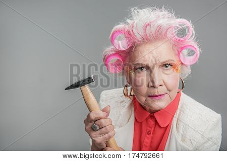 I can fix anything. Portrait of Angry older woman with extravagant makeup holding hammer. isolated on gray background