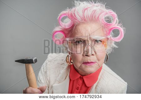 Ready for renovations. Waist up portrait of Elderly stylish female standingwhile holding hammer in her hand. isolated on gray background