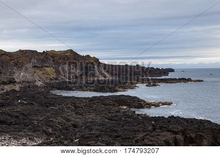 Melancholic Iceland Landscape With Black Volcanic Lava Fields On The Sea Shore, And View Over Atlant