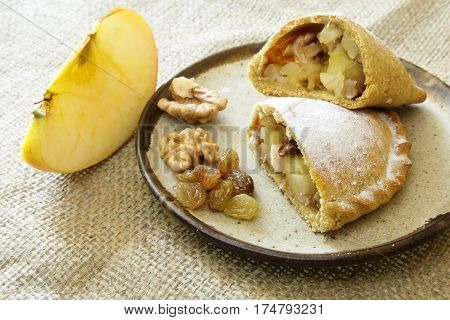 Russian pirozhki, baked patties or pies on basket with nuts and apples