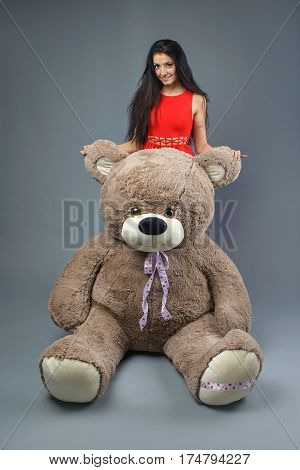 Young beautiful girl with big teddy bear soft toy happy smiling and playing on grey background